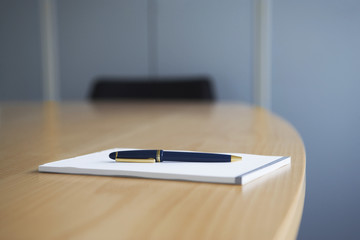 Ballpoint pen and notepad on conference table