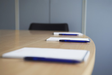 Ballpoint pens and notepads on conference table