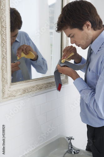 Man scrubbing stain from tie, by sink