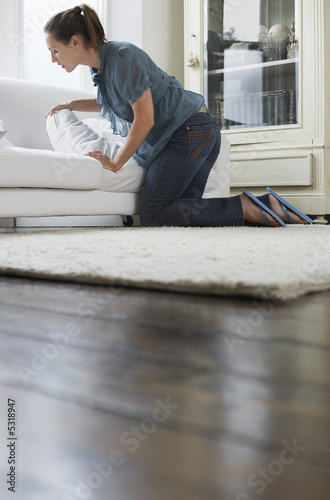 Woman searching in couch cushions