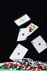 Playing cards falling on pile of gambling chips, in studio