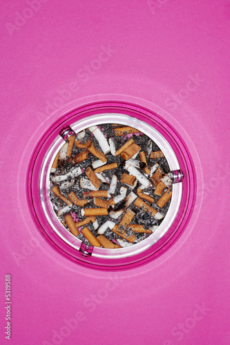 Full ashtray on pink background, view from above