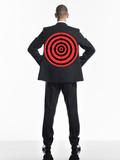Young businessman with target on back, back view