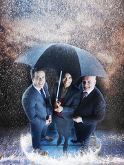 Businesspeople under one umbrella