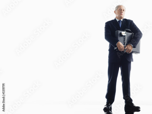 Businessman holding chained briefcase