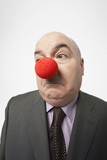 Bald businessman Wearing Clown Nose, frowning