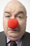 Bald businessman Wearing Clown Nose, frowning, close-up