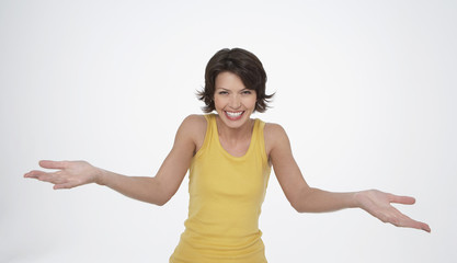 Enthusiastic woman smiling big, arms stretched out in front, palms up