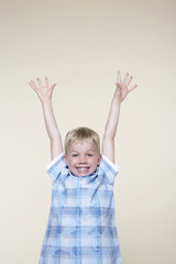 Smiling, excited boy standing with Arms Raised