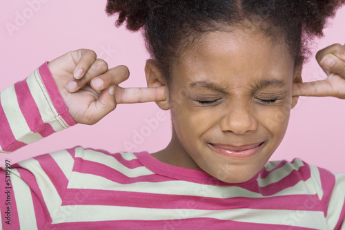 Girl with eyes closed, putting Fingers in Ears, close-up