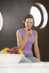 Woman eating apple, sitting on kitchen surface