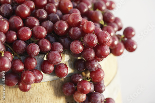 Red grapes arranged on wine cask, close-up