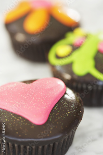 Three cupcakes on kitchen surface