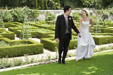Bride and groom walking hand in hand in garden