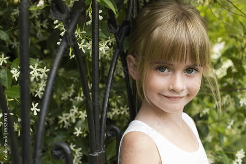 Young girl leaning on fence, smiling, portrait