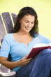 Smiling female sitting in chair reading book.