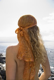 Back view of nude woman with wavy hair and head scarf at coast. poster