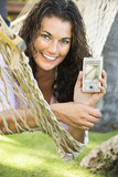 Smiling female in hammock holding up PDA towards viewer. poster