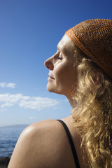 Profile of woman with wavy hair and head scarf at coast.