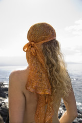 Back view of nude woman with wavy hair and head scarf at coast.