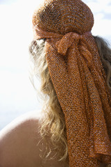 Back view of woman with wavy hair and head scarf.