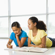 Two preteen girls lying on floor doing homework together.