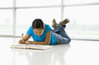 Asian preteen girl lying on floor doing homework.
