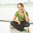Caucasian preteen girl sitting on floor talking on cell phone.