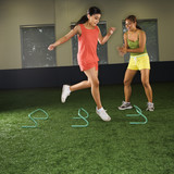 Girl jumping step hurdles while woman coach watches. poster