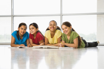 Preteen girls sitting together on floor with schoolwork.