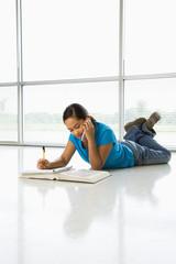 Asian preteen girl doing homework while talking on cell phone.