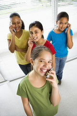 Preteen girls talking on cell phones and looking at viewer.