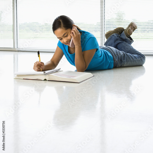 Asian preteen girl doing homework while talking on cell phone.