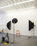 Studio shot of photographic lights aimed at red plastic chair. poster