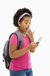 Girl with backpack looking at phone with surprised expression.