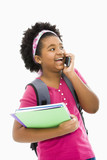 Girl with books and wearing backpack talking on cell phone.