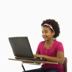 Girl sitting in school desk typing on laptop computer.