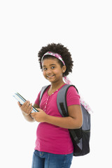 Girl holding books and wearing backpack smiling at viewer.