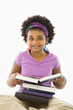 Girl with large stack of books smiling at viewer.