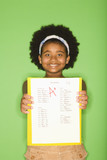 Girl holding out graded school assignment smiling proudly. poster