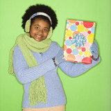 girl in winter clothing holding wrapped package. poster