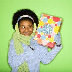 girl in winter clothing holding wrapped package.