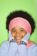 girl in winter clothing with gloved hands to face smiling.