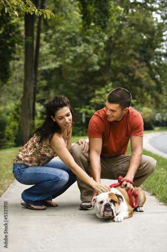 Couple petting dog.