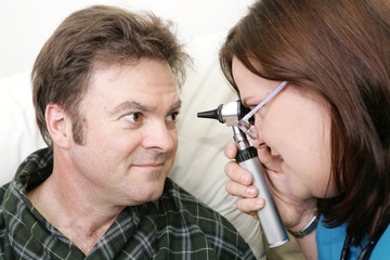 Nurse examining her patient's eyes with an ophtalmoscope.