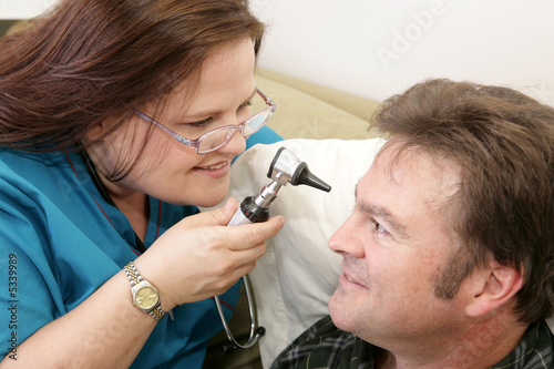 Home health nurse checking her patient's  eyes