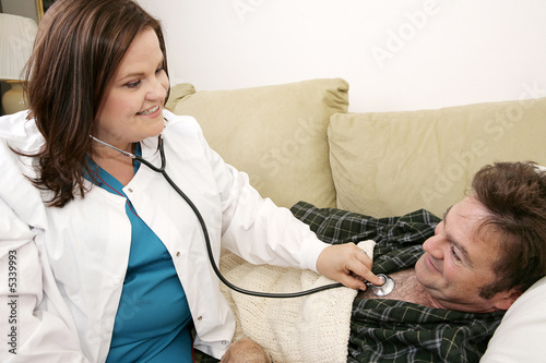 Friendly home health care nurse listing to her patient's chest