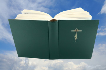 Opened holy bible over sky with clipping path, isolated