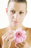 female with dreamy expression holding flower poster