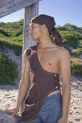 Young man dressed in rustic clothing on the beach